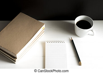 Workplace with notepad, book and cup of black coffee on white wooden table.