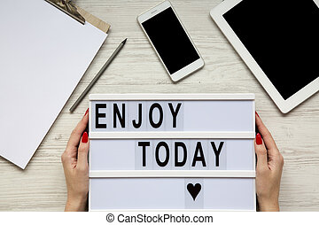 Workplace with tablet, smartphone, notepad and 'Enjoy today' word on lightbox over white wooden background, top view. Female hands hold lightbox. From above, flat-lay, overhead.
