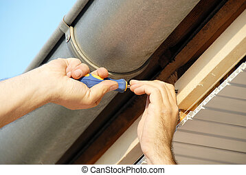Works on house - working hands screwing up under house roof...