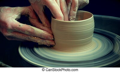 Workshop molding of clay on potter's wheel. Dirty hands in the clay.