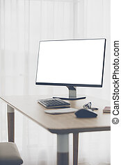 Workspace background with desktop pc and office accessories on table, White screen on monitor.