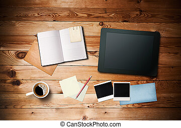 Workspace with coffee cup, tablet pc, instant photos, note paper and notebook on old wooden table