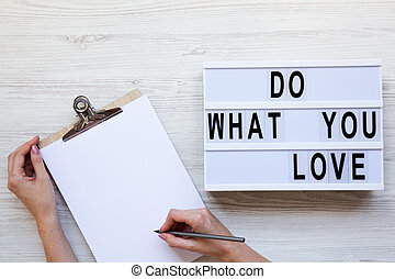Workspace with female hands, clipboard and 'Do what you love' word on lightbox over white wooden background, top view. From above, flat-lay, overhead.