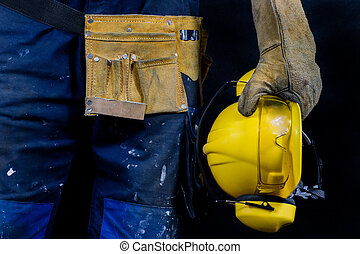 Workwear for production workers. A construction worker holding protective accessories.
