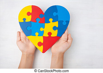 World Autism Awareness day, mental health care concept with puzzle or jigsaw pattern on heart with child's hands