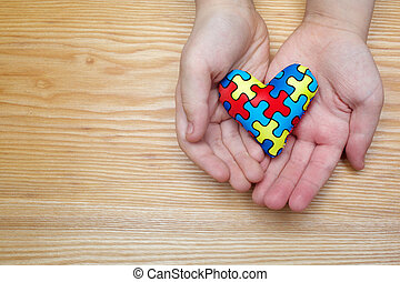 World Autism Awareness day, puzzle or jigsaw pattern on heart with autistic child's hands
