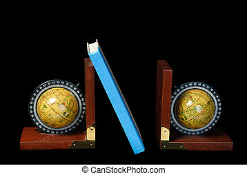 Two world globe bookends holding up a book, isolated against a black background