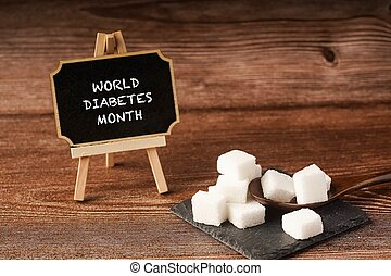 ?World Diabetes Month? wordings on a chalkboard with sugar cubes