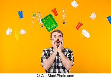 World Environment Day, plastic recycling problem and environmental disaster concept - Terrified man on yellow background with trash