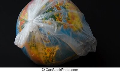 World Environment Day. The earth in a plastic bag. Polyethylene disposable package. Global warming due to pollution by plastic debris. The concept of Earth Day.