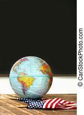 World globe, American flag on school desk