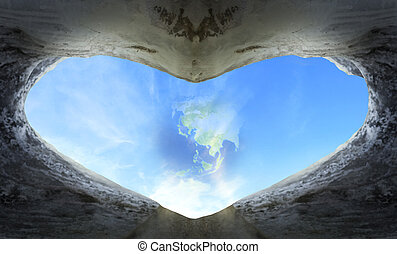 World Heart Day concept: heart shaped cave in the background of blue sky with clouds