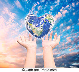 World in heart shape with over women human hands on blurred natural background: World Heart health day, Element of this image furnished by NASA