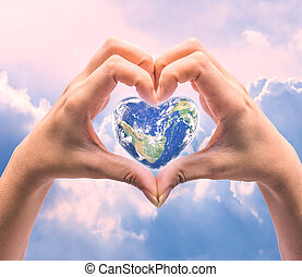 World in heart shape with over women human hands on blurred...