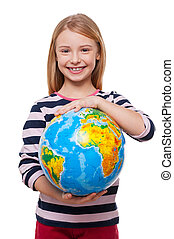 World in my hands! Cheerful little girl holding a globe and smiling while standing isolated on white