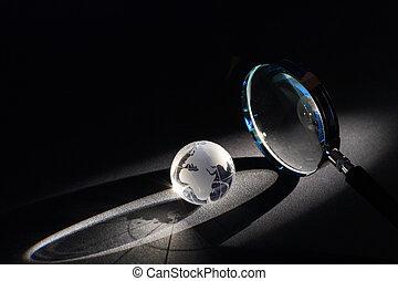 World Investigation - Magnifying glass and globe on dark...