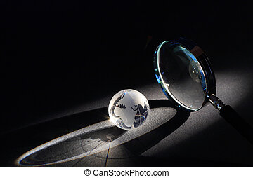 World Investigation - Magnifying glass and globe on dark...