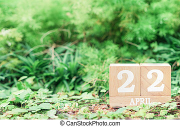 "World Mother Earth day background concept. Wooden calendar with date ""22 april"" with green nature background with copy space."