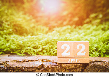 "World Mother Earth day background concept. Wooden calendar with date ""22 april"" with green nature background"