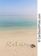 World RELAX written on sand early in the morning on cristal clean beach of Maldives
