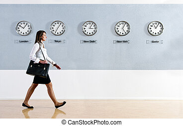 World Time - Business woman walking hurrily past a row of...