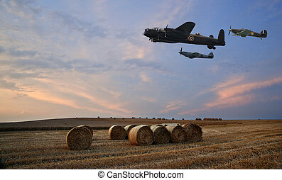 World War 2 RAF airplanes floying over lovely sunset golden hour landscape of hay bales in field in English countryside