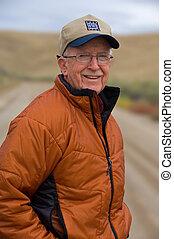 World War II veteran - Senior man wearing a cap showing off...
