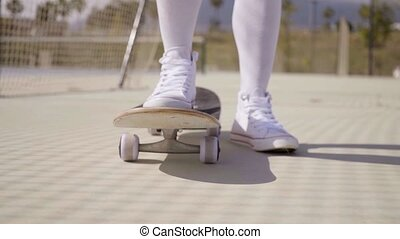 Worms eye view of skater wearing white gym shoes with one...