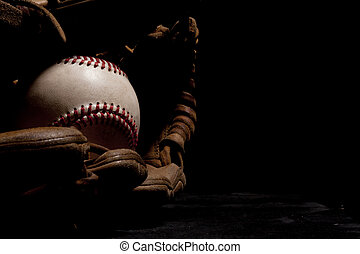 Dramatic lighting of an old baseball and glove isolated on black background.
