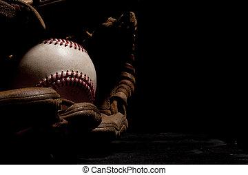 Worn Baseball and Glove - Dramatic lighting of an old...