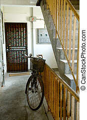 Worn bicyle at pathway of residential building