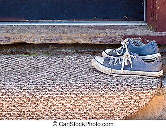 Worn blue tennis shoes on doormat - Pair of old tied blue...