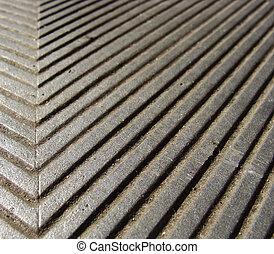 worn metal grid seal on a sidewalk