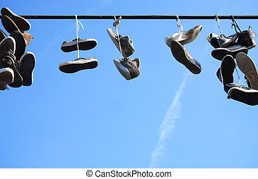 Lot of worn shoes hanging on wire against blue sky