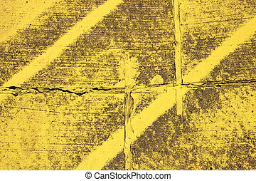 Worn texture with yellow stripes on asphalt