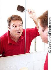 Worried About Baldness - Mature man in his forties uses a...