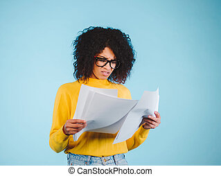 Worried african american businesswoman reading a notification standing on blue background in yellow wear and afro hairstyle.