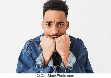 Worried african man in denim jacket covering mouth with fists
