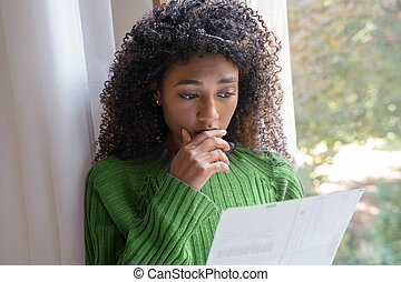 Worried black woman reading a layoff notice at home