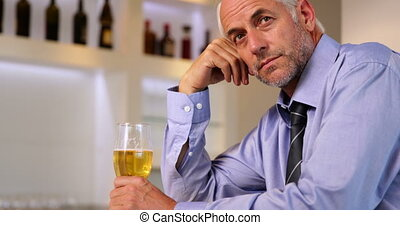 Worried businessman drinking a beer after work at the local...