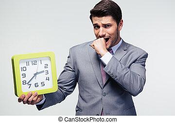 Worried businessman holding clock