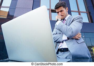 Worried businessman looking at laptop