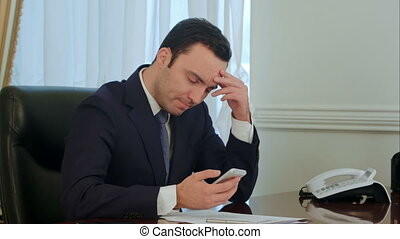 Worried businessman looking on smartphone and reading bad...