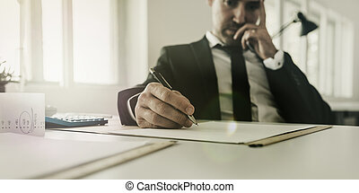 Worried businessman sitting at his desk working on tax and financial paperwork