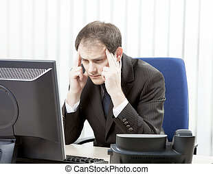 Worried businessman with a headache sitting at his desk ...