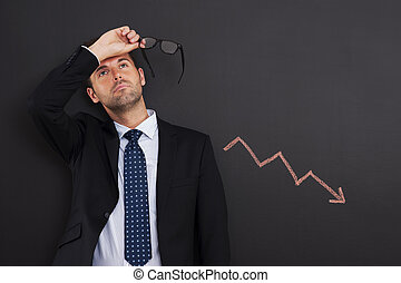 Worried businessman with sign of decreased profit