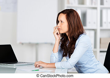 Worried businesswoman sitting at her desk staring into the ...
