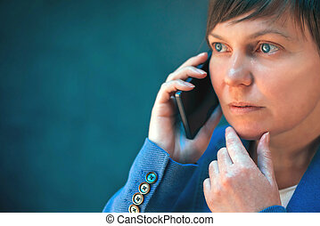 Worried businesswoman talking on mobile phone