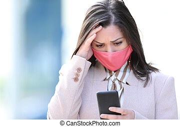 Worried businesswoman with mask reading phone content
