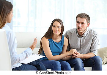 Worried couple listening to marriage counselor during a...